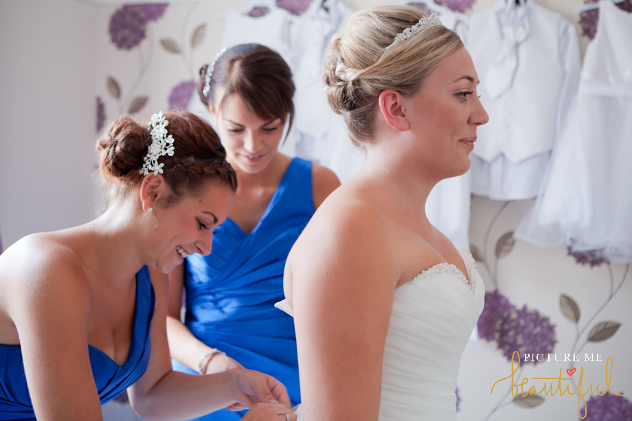bridesmaids getting the bride ready by Picture Me Beautiful Wedding Photography and Film